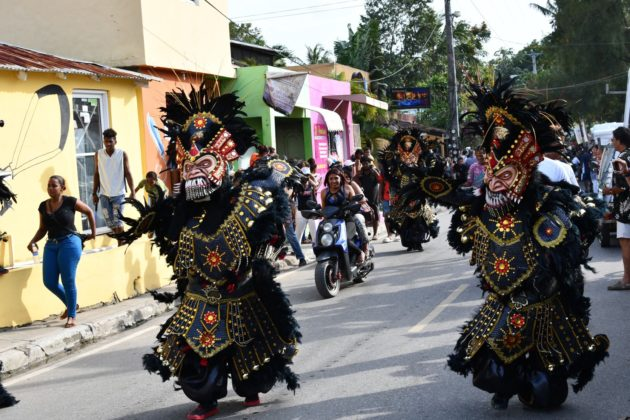 dark dressed devils parading in the carnival of Cabarete