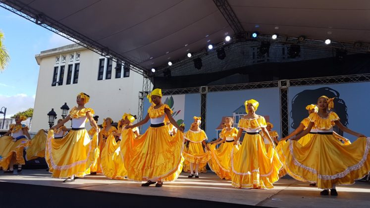 Dominican folk dancers in yellow dresses