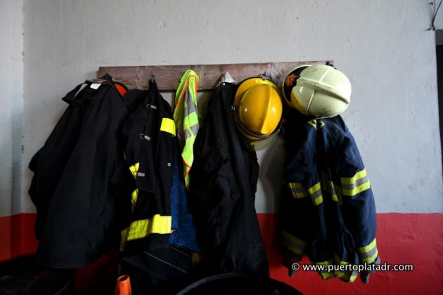Firefighters apparel and hats hang in a wall
