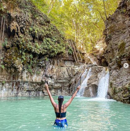 A woman opens her arms enjoying the natural scenes