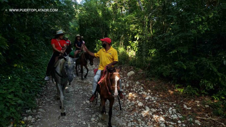 A horseback riding tour guide with customers